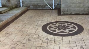 Printed Concrete Patio in a Blended Biscuit and Bideford Buff Ashlar Slate with Pin-Wheel Feature with Brick Edge