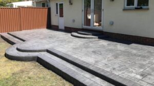 DCS Printed Concrete Patio in Platinum Grey Grand Ashlar with Steps and Tinted Brick Edge